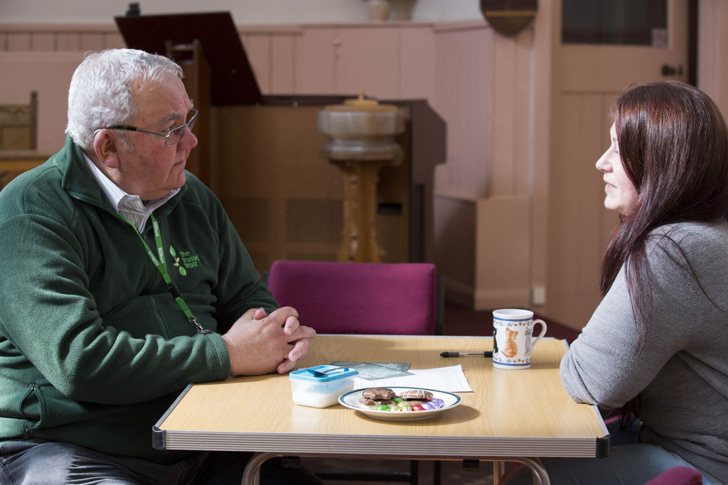 voluteer chatting to client over tea and biscuits